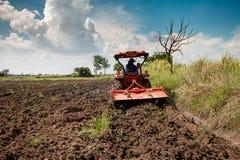 Trattore per l'agricoltura il campo del workingon e del fondo del cielo Fotografie Stock Libere da Diritti