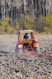 Trattore rosso che ara in autunno, campo della preparazione per piantare Fotografia Stock