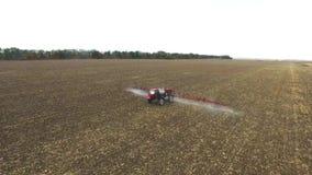 Trattore rosso che ara il cereale di campo Colpo aereo archivi video
