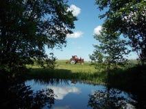 Trattore rosso che funziona in un paesaggio di paesaggio Fotografia Stock Libera da Diritti