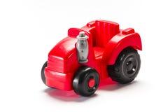 Trattore rosso del giocattolo da una plastica Fotografie Stock Libere da Diritti