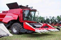 Trattore rosso di tecnologia moderna che ara un campo agricolo verde in primavera dell'azienda agricola Grano della semina della  Fotografia Stock