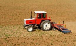 Trattore rosso e bianco con una macchina del coltivatore dell'attrezzo della zappa come rimorchio su un campo della terra con le  Fotografie Stock