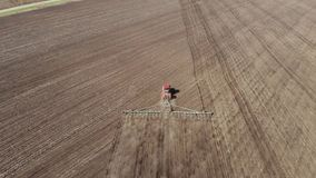 trattore rosso moderno del metraggio aereo 4K sul campo agricolo il giorno soleggiato Trattore che ara sbarco Coltivazione del tr video d archivio