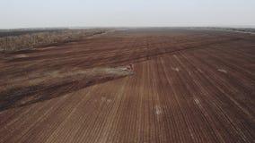 trattore rosso moderno del metraggio aereo 4K sul campo agricolo il giorno soleggiato Trattore che ara sbarco Coltivazione del tr archivi video