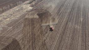 trattore rosso moderno del metraggio aereo 4K sul campo agricolo il giorno soleggiato Trattore che ara sbarco Coltivazione del tr stock footage