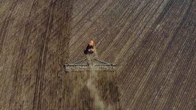 Trattore rosso moderno del metraggio aereo sul campo agricolo il giorno soleggiato Trattore che ara sbarco Coltivazione del tratt archivi video