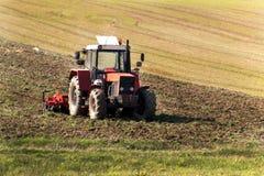 Trattore rosso nel campo Lavoro agricolo dell'azienda agricola Agricoltura in repubblica Ceca Fotografia Stock