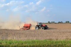 Trattore sul campo aratura Polvere sul campo scavo Trattore rosso aratro Immagine Stock