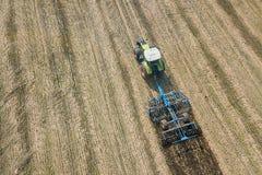 Trattore sul lavoro, coltivante un campo, antenna del coltivatore di semenzaio Fotografia Stock