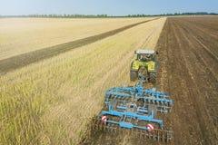 Trattore sul lavoro, coltivante un campo, antenna del coltivatore di semenzaio Fotografia Stock Libera da Diritti