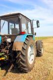 Trattore in un campo, scena agricola in estate Immagine Stock