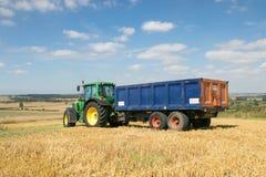 Trattore verde moderno che tira un rimorchio nel campo del raccolto Immagine Stock Libera da Diritti