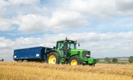 Trattore verde moderno che tira un rimorchio nel campo del raccolto Fotografie Stock Libere da Diritti