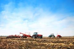 Trattori con i carri armati nel campo Macchinario agricolo e coltivare Immagini Stock Libere da Diritti