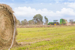 Trattori e Hay Roll in un campo Fotografia Stock