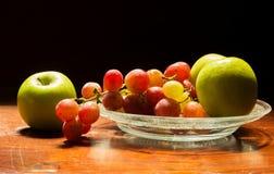 Traube und Apfel auf Teller Stockfotos