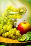 Trauben im Glas, im roten Apfel und in der Kiwi Lizenzfreie Stockfotografie