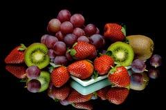 Trauben, Kiwi und Erdbeeren auf einem schwarzen Hintergrund Stockbilder