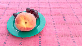 Trauben mit Pfirsich in einer Platte Lizenzfreie Stockbilder