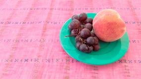 Trauben mit Pfirsich in einer Platte Stockbild