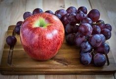 Trauben und Apfel auf einem hölzernen Brett Stockfotografie