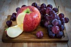 Trauben und Apfel auf einem hölzernen Brett Stockfotos