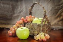 Trauben und grüner Apfel mit altem Korb Stockfoto