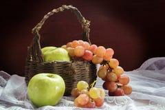 Trauben und grüner Apfel mit altem Korb Stockfotografie
