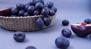 Trauben und Pflaumen in einer silbernen Schüssel auf einem dunklen Hintergrund lizenzfreie stockfotos