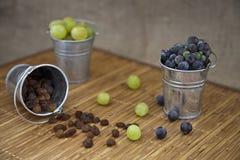 Trauben und Rosine in den Eiseneimern Stockbilder