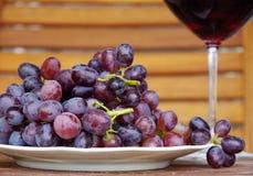 Trauben und Wein im Glas Stockbild