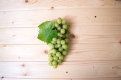 Trauben von Trauben auf einem Holztisch Lizenzfreie Stockfotos
