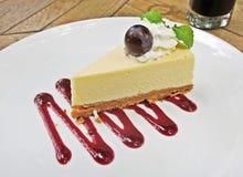 Traubenkäsekuchen mit süßer Traubensoße auf weißer Platte Lizenzfreies Stockbild