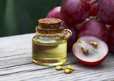 Traubenkernöl in einem Glasgefäß und in frischen Trauben auf altem Holztisch Flasche organisches Traubenkernöl für Badekurort und Lizenzfreies Stockbild