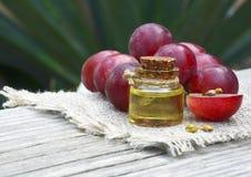 Traubenkernöl in einem Glasgefäß und in frischen Trauben auf altem Holztisch Flasche organisches Traubenkernöl für Badekurort und Lizenzfreie Stockbilder