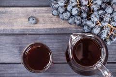Traubensaft im Krug und im Glas, Draufsicht der blauen Trauben Lizenzfreie Stockfotografie