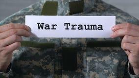 Trauma di guerra scritto su carta in mani del soldato maschio, concetto di PTSD, primo piano video d archivio