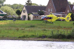 Trauma helicopter landing. Trauma helicopter is landing on the other site of the river ijssel to assist the paramedics who are giving first aid to the people Royalty Free Stock Photos