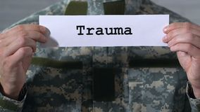 Trauma written on paper in hands of male soldier, mental and physical health. Stock footage stock video