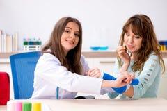 Женский traumatologist доктора перевязывая женского пациента стоковые фото
