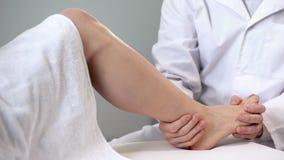 Traumatologist die geduldige enkel bewegen, beoordeling van strengheid van verwonding, close-up stock foto