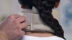 Traumatologist die vrouwelijke geduldige schuim cervicale kraag, verwondingsbehandeling toepassen stock video
