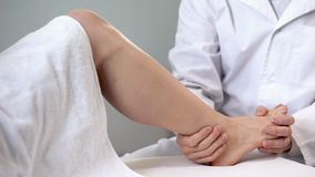 Traumatologist moving patient ankle, assessing severity of injury, closeup stock photo
