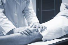 Traumatologist orthopedic surgeon doctor examining patient Stock Images