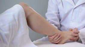 Traumatologist que examina la pierna paciente, evaluación de la severidad de lesión, salud almacen de metraje de vídeo