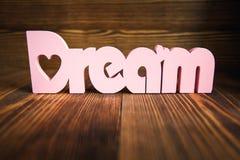 Traumbuchstaben auf hölzernem Hintergrund stockbild