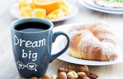 Traumgroßes Becher Frühstück des gutenmorgens Kaffee mit Hörnchen, Nüssen und Orangen Stockfoto