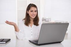 Traumjob: erfolgreiche Geschäftsfrau, die am Schreibtisch mit Laptop sitzt Lizenzfreie Stockfotos
