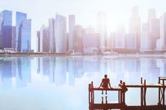 Traumkonzept, Mann, der auf dem Pier sitzt und modernes Stadtbild genießt stockbilder